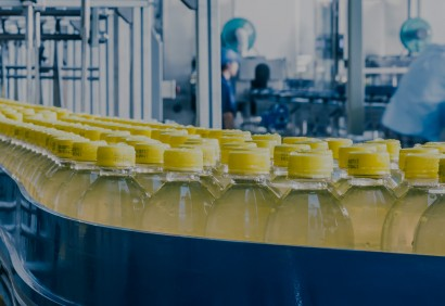 assembly line of capped bottles with yellow liquids