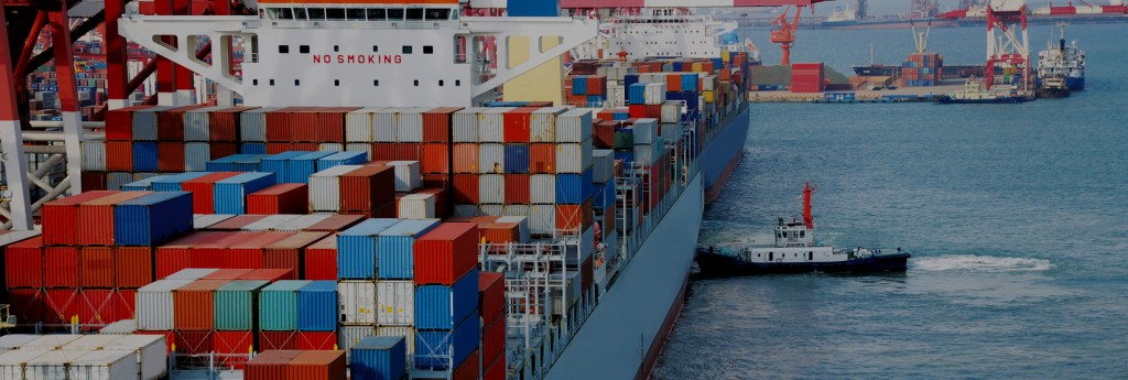 boat approaching cargo ship full of containers