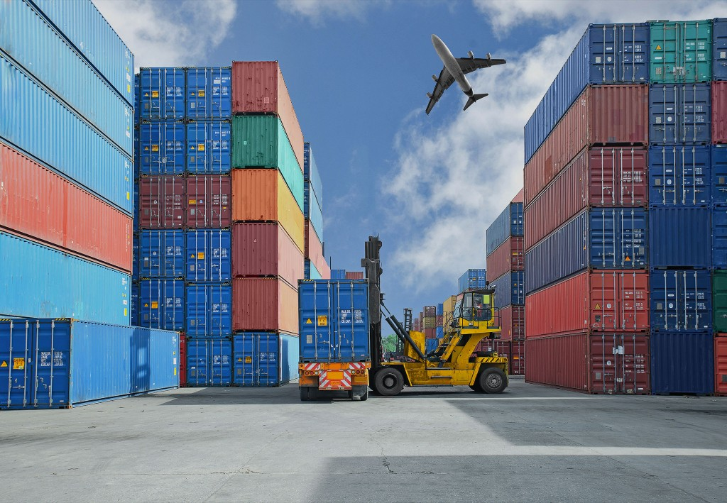 shipping yard with forklift lifting container onto truck and plane in the sky